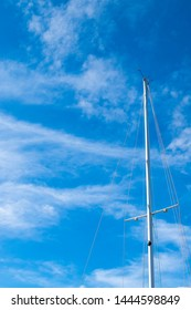 The top of a sailboat with the sails removed, showing the masthead, spreaders, shrouds, forestay, and mast against a blue sky.