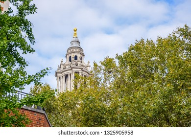 Top of Saint Paul's Cathedral through trees on Ludgate Hill at the highest point of the City of London, England, United Kingdom