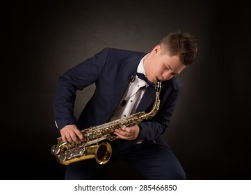Top saxophonist playing sax during a live jazz session. Man in navy blue suit performing on festival.