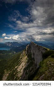 Top of Schafberg mountain and view on Attersee on a sunny day with dramatic cloudy blue sky