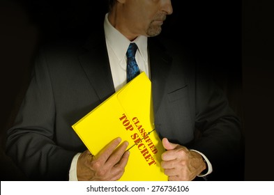Top Secret Classified business, legal and government concept showing a man in a black suit pulling a Top Secret folder dossier out of his jacket. Dramatic lighting highlights the Top Secret folder
