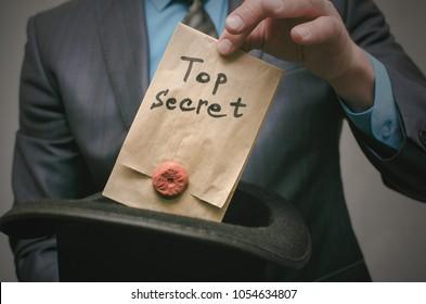 Top secret concept. Open the secret. Business man takes out secret documents from his hat. Confidential dossier information. Super important information.
