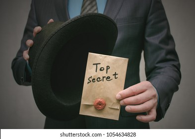 Top secret concept. Open the secret. Business man takes out secret documents from his hat. Confidential dossier information. Super important information.