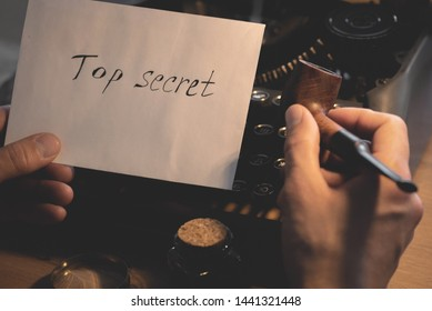 Top secret document letter and a smoking pipe in a detective spy agent hands on a table background.