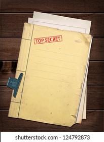 top secret file on wooden table.