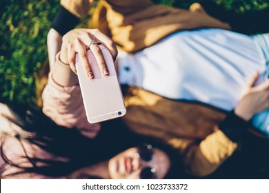 Top select focus on woman's hand holding modern digital telephone device and making selfie photos for social networks together with friend lying outdoors on green grass enjoying sunny weather