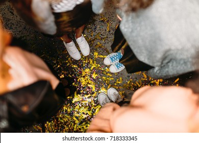 Top shot of four unrecognizable women standing on floor with confetti