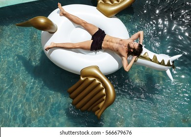 Top shot of handsome male model posing topless on air bed keeping hands behind his head, looking relaxed and carefree. Young fit man sunbathing on inflatable mattress, floating in hotel swimming pool