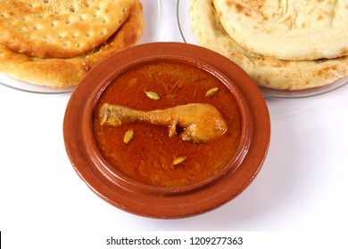 Top shot of Qourma Salan, Indian food, Top view of Chicken Qorma dish with cardamom and Naan or sheermal on white background, Ramzan iftar meal, Ramadan dinner.