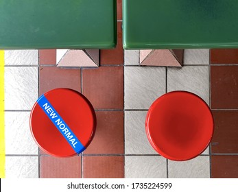 Top shot of tables and chairs seats at Singapore hawker food centres. Social distancing tape on seat. 'New Normal' text digitally added. No dining during outside covid-19 coronavirus outbreak