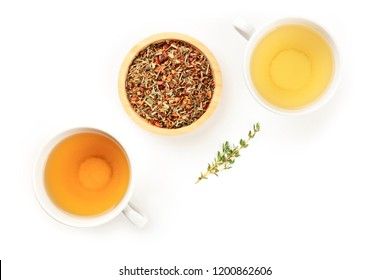 A top shot of two tea cups with dry loose tea leaves and a thyme branch, on a white background with a place for text