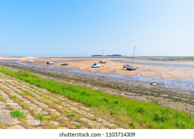 From the top of a sloping grass bank out across the estuary at low tide, where small yachts and motor boats sit on the sand, out across the salt marshes to the horizon