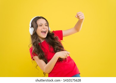Top songs. Child teen enjoy music playing in earphones. Little girl enjoying favorite music. Catch the rhythm. Kid listening music headphones. Entertainment and fun. Whole musical world in her ears.