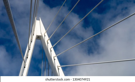 Top spire of the Northern Spire bridge in Sunderland, showing cables and the white metal apex structure against the blue sky. Taken in the Spring sunshine with blue sky and white clouds.