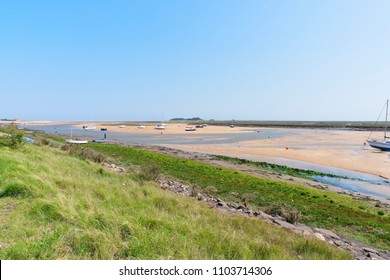 From the top of a steep grass bank, looking out at the yachts beached in the estuary at low tide.