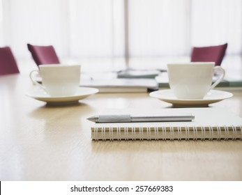 Top of table with coffee and book with Blurred conference room interior background