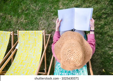 Top of teenage girl in red shirt and wide-shoulder hat holding and reading blank book or magazine on chair beach in green garden.