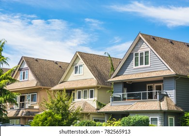 Top of three residential houses on blue sky background