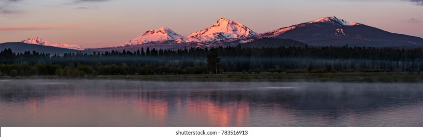 The Top of the Three Sisters Mountains and Mt. Bachelor turn Pink at Sunrise viewed from the Lake at Black Butte Ranch, Extra Wide Panorama