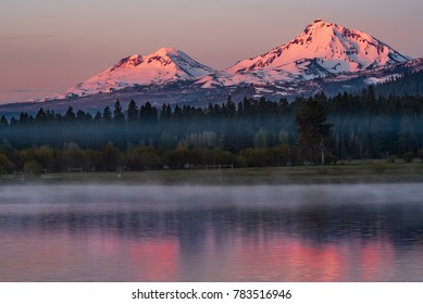 The Top of the Three Sisters Mountains turn Pink at Sunrise viewed from the Lake at Black Butte Ranch, Closeup, Horizontal