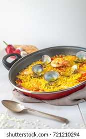 Top tilted lower view of a delicious  seafood and red pepper Paella rice dish from Spain with one spoon and against a wooden background