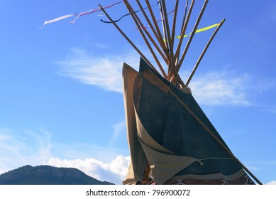 The top of traditional lodging of North American First Peoples (Native Americans/American Indians) from Plains regions. Ribbons blowing in breeze on top of lodge poles.