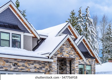 The top of a typical american home in winter. Snow covered roof and nice window.
