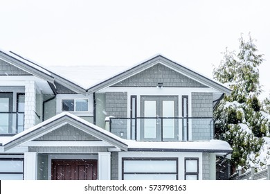 The top of a typical american home in winter. Snow covered roof and nice window. Heavy snowfall over entire picture frame.
