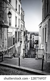 From the top of a typical staircase in Montmartre Hill, we see Paris skyline in the background. Black and white.