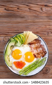 Top vertical view of ketogenic diet breakfast on the white plate on wooden background with copy space