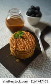 Top vertical view on delicious Belgium Dutch waffle cookies caramel sauce with mint on wooden board bowl of blackberries and spoon on natural color tablecloth