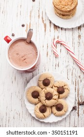 Top vertical view of plate of snickerdoodle cookies, hot chocolate, peppermint candy cane, and chocolate peanut blossom cookies on weathered white wood