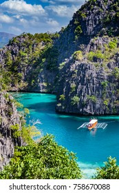 Top vertical view to tropic turquoise  lagoon with rocks ana traditional boats near Kayangan Lake, Coron, Palawan, Philippines