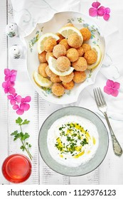 Top vie shot of plate with falafel and dip sauce with yogurt, tahine and parsley.