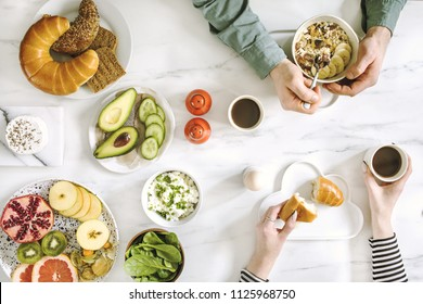 The top viev of super food on the white marble table. Flat lay. Variuos vegetables ingredients and healthy food for vegetarians. Perfect sunday morning breakfast for couple..