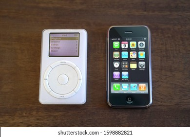 Top view of a 1st generation iPod and iPhone sitting on top of a wooden table with the main displays turned on. Take December 26, 2019. San Francisco, CA.