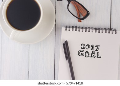 top view of 2017 goal written on notebook,pen,coffee,glasses on the white desk