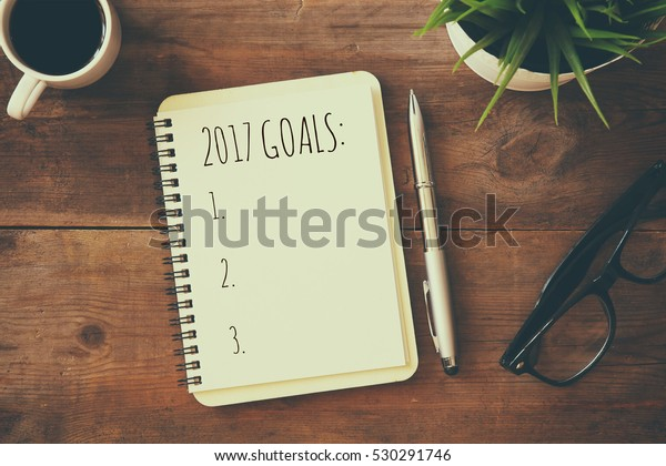 Top view 2017 goals list with notebook, cup of coffee on wooden desk