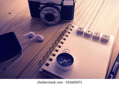 Top view of  2017 on wooden block written on the notebook,travel planning concept.note book,compass,passport,film camera on the wooden desk.