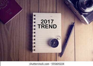 Top view of 2017 TREND written on the notebook,travel planning concept.note book,compass,passport,film camera on the wooden desk.