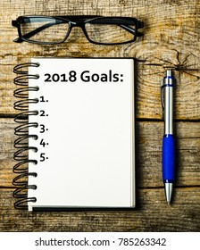 Top view 2018 goals list with notebook on wooden desk
