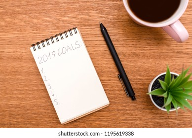 Top view 2019 goals list with notebook, cup of coffee on wooden desk