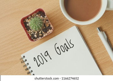 Top view of 2019 goals on notebook with cactus and hot coffee on wood table on white wall background,flay lay.