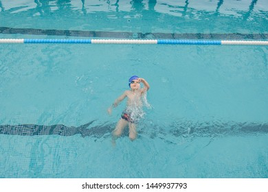 top view of a 7-year boy swimming backstroke in a swimming pool