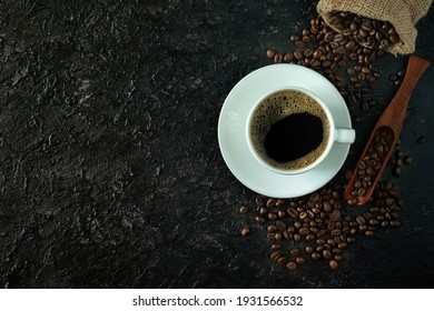 Top view above of Black hot coffee with milk foam for morning beverage menu in white ceramic cup with coffee beans roasted in burlap sack bag on dark grunge table background. Flat lay with copy space.