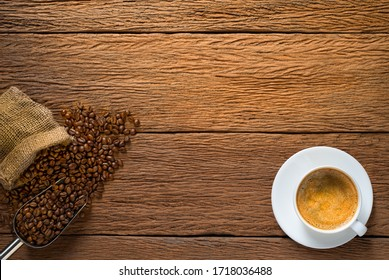 Top view above of Cappuccino or latte hot coffee with milk foam for morning menu in white ceramic cup with coffee beans roasted in burlap sack bag on wood table background. Flat lay with copy space.