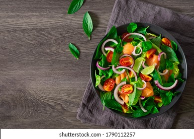 Top view from above fresh Salmon salad and tomato, onion with spinach, lettuce and basil in black bowl on dark background. Healthy tasty food, homemade concept. Flat lay with copy space.