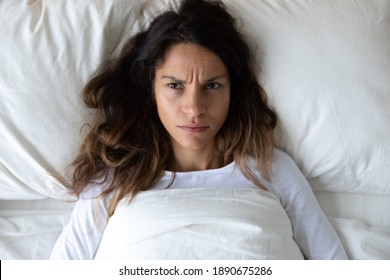 Top view from above unhappy annoyed woman lying under blanket in bed alone, suffering from insomnia concept, noisy neighbors, depressed young female thinking about problems, feeling unwell