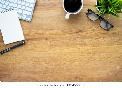 Top view above of Wooden office desk table with keyboard, coffee cup and notebook, glasses with equipment office supplies. Business and finance concept. Workplace, Flat lay with blank copy space.