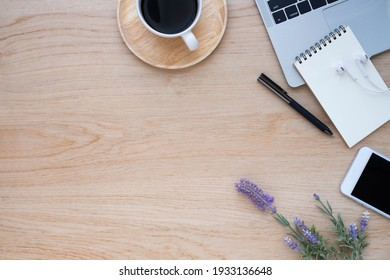 Top view above of Wooden office desk table with keyboard of laptop and notebook with equipment other office supplies. Business and finance concept. Workplace, Flat lay with blank copy space.